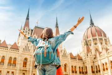 Perfect cities for a long layover: Happy asian casual woman student enjoying great view of the Parliament building in Budapest