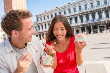 The most romantic places in Italy: Happy couple laughing eating ice cream on vacation travel in Venice, Italy.